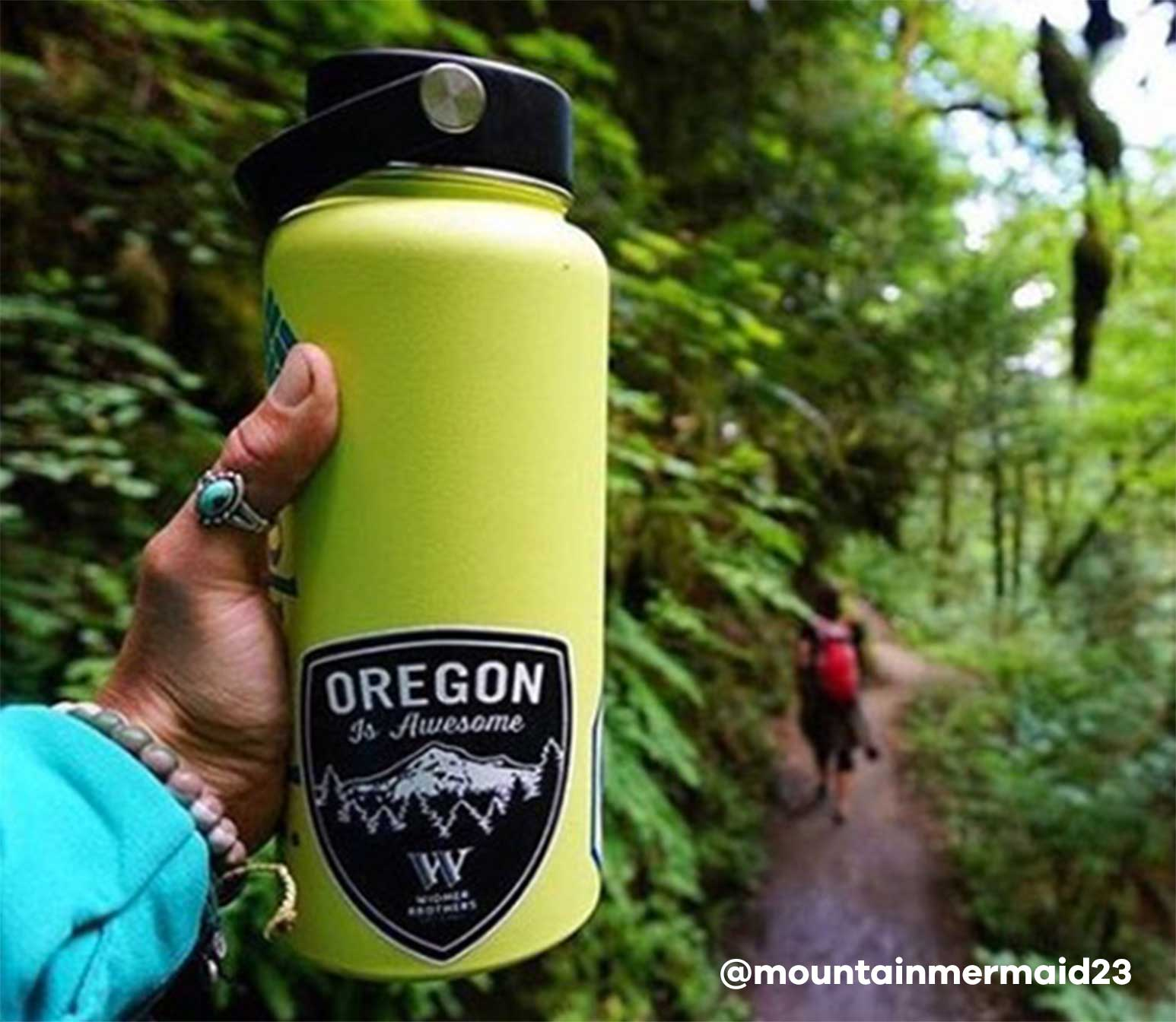 Person holding up green Hydro Flask bottle
