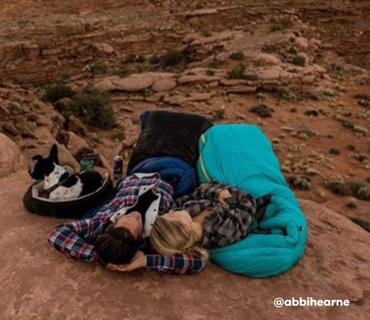 Couple lying in sleeping bags in canyon looking at sky