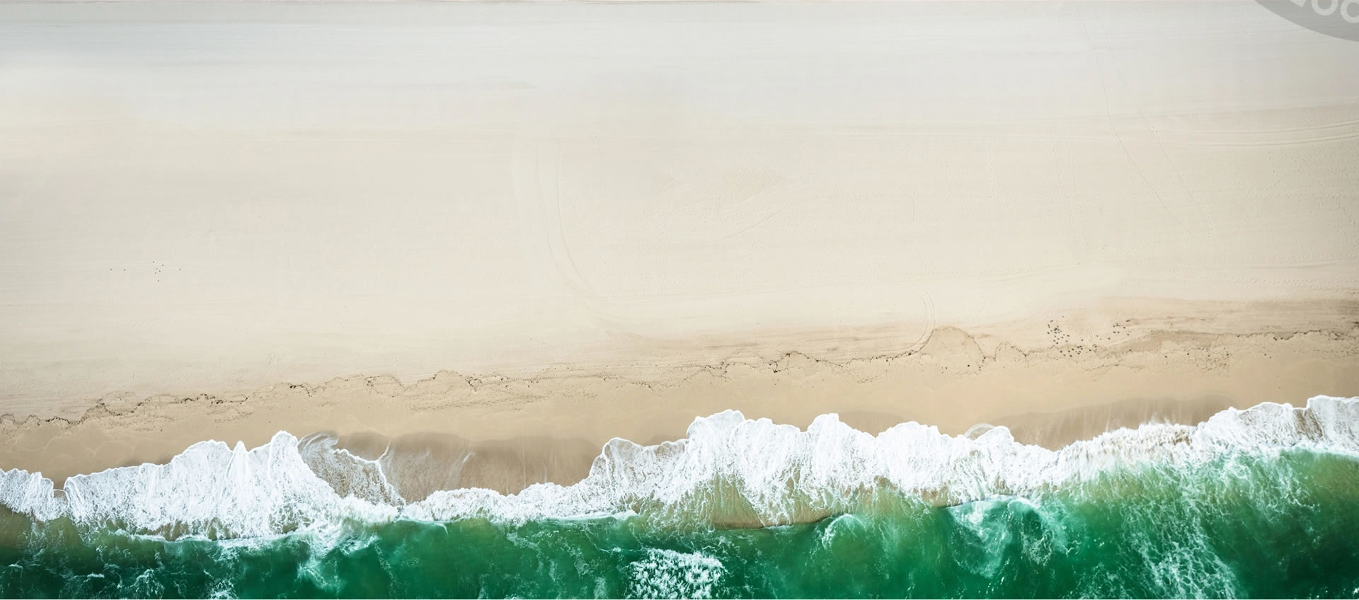 An aerial image of the ocean waves wash up on the shore of a clean, sandy beach.