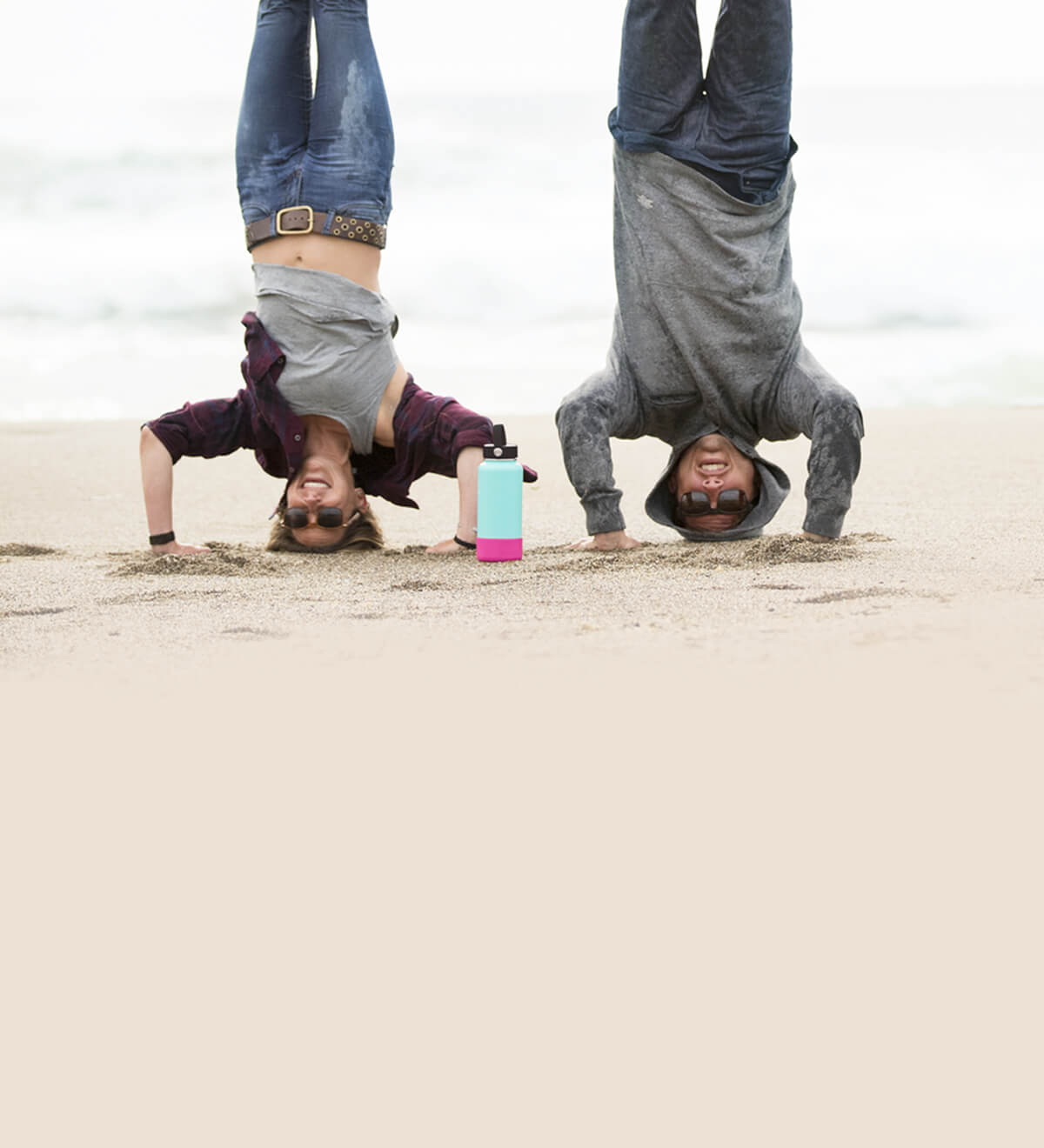 Two friends handstand on the beach with their 32 oz Hydro Flask equipped with a Boot for extra protection.