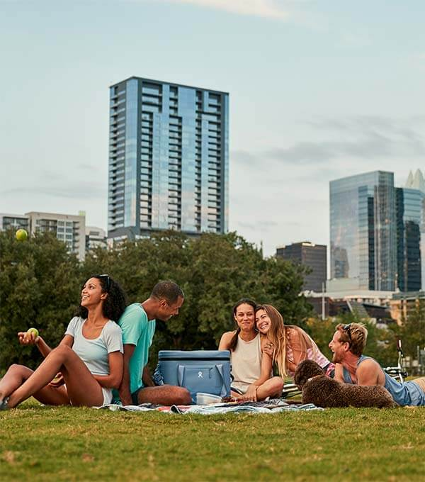 Friends gather around a Hydro Flask Soft Cooler Tote while picnicking in the park.