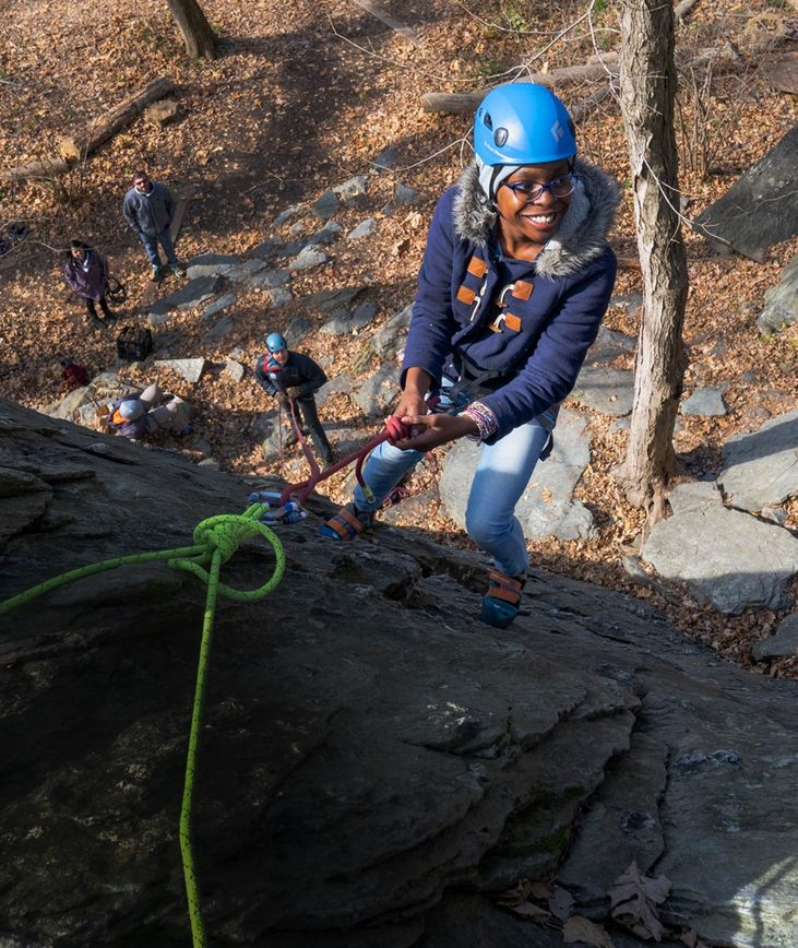A middle school student rock climbs in Carderock Recreation Area.